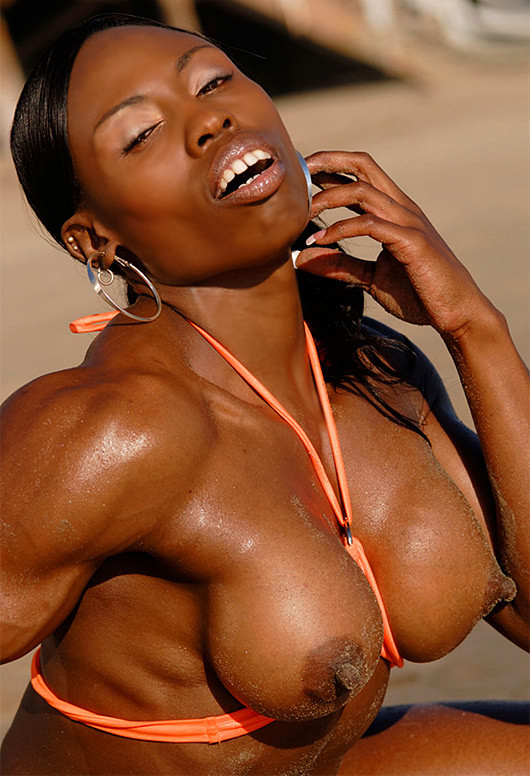 Black muscular Mistress sexy bikini posing on the beach